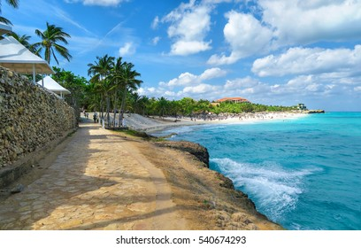 beautiful seascape of turquoise Atlantic Ocean, sandy coast of Varadero, Cuba, coconut palm trees lining up the beaches, amazing blue sky, white clouds and superb resorts close to the ocean