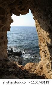Beautiful seascape view through loophole of Monemvasia medieval castle overlooking the Aegean sea. Monemvasia, Peloponnese, Greece, June 2018.