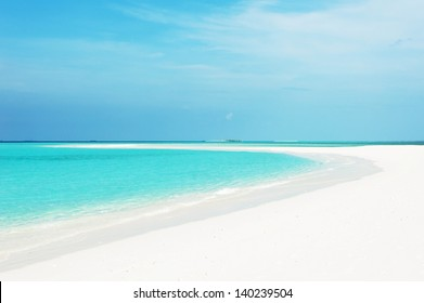 Beautiful seascape with white sand on the beach and blue water on the sea