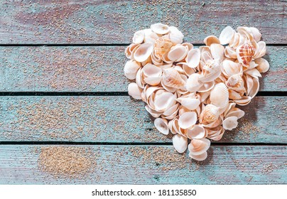 Beautiful seashell heart formed of multiple small bivalves, cones and conches on rustic weathered wooden boards with copyspace for a nautical Valentines or anniversary greeting