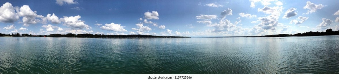 Beautiful seaside of Ammersee on a sunny day with turquoise water and white clouds, Germany