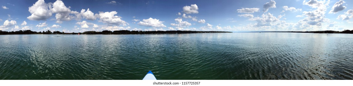 Beautiful seaside panorama of Ammersee with a stand up paddle board on a sunny day with blue sky and clouds, Germany