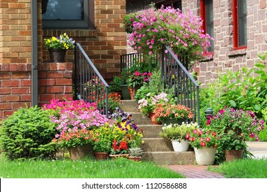 Beautiful seasonal house outdoor decoration. Scenic view with way to the main entrance  and staircase of the old style house decorated by colorful potted flowers for spring and summer season.