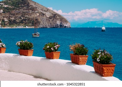 Beautiful seaview with touristic boats and cape in Sant Angelo from the promenade along the sea, Ischia, Italy.