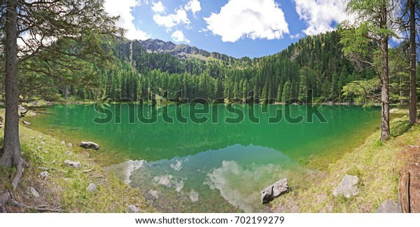 A beautiful secluded mountain lake with turquoise crystal clear water, surrounded by forest. Picturesque landscape panorama. Steiermark, Austria.