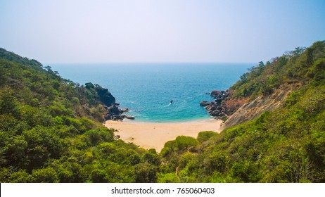 Beautiful secret beach Butterfly in Goa, India. Aerial view of pristine beach with rocky bay and waves crashing