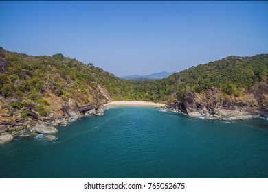 Beautiful secret pristine beach Butterfly in Goa. Aerial view of beach with rocky bay and waves crashing