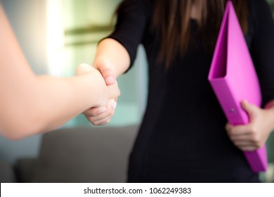 Beautiful secretary is glad to welcome Boss's customer by handshake and customer feel happy or secretary receives a guest or visitor at her workplace or office. She love service and happy with her job