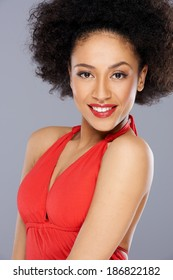 Beautiful seductive African American woman with a big afro hairstyle wearing a low cut red dress looking at the camera with parted lips