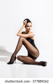 Beautiful, seductive woman sitting in sexy pose wearing alluring stockings and heels over isolated background.
