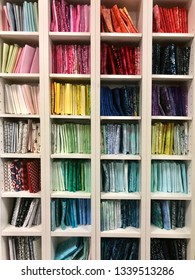 A beautiful selection of fabric fat quarters in a tall shelving unit at a local quilt shop.