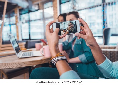 Beautiful selfie. Selective focus of a smartphone screen with photo of happy beautiful women