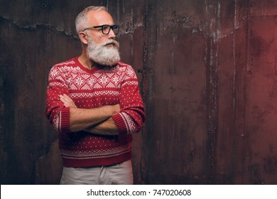 Beautiful senior bearded man in Christmas sweater looking away. Santa Claus wishes Merry Christmas
