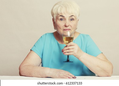 A beautiful senior blond woman in a blue dress is holding a glass of white wine. Copy space.