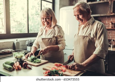 Beautiful senior couple in aprons is talking and smiling while cooking together in kitchen