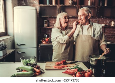 Beautiful senior couple in aprons is tasting food and smiling while cooking together in kitchen