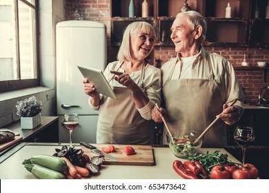 Beautiful senior couple in aprons is using a digital tablet, talking and smiling while cooking together in kitchen