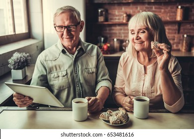 Beautiful senior couple is drinking tea, eating cookies, using a digital tablet and smiling while resting in kitchen