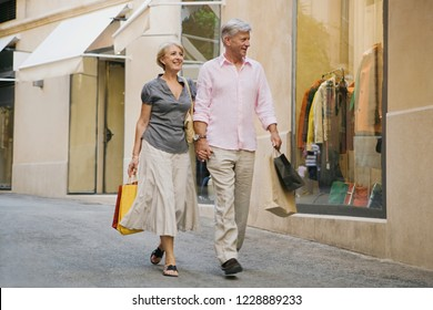 Beautiful senior couple holding hands walking in luxury shopping street carrying bags, vacation trip, outdoors. Healthy mature consumer people on city break travel, leisure recreation lifestyle.