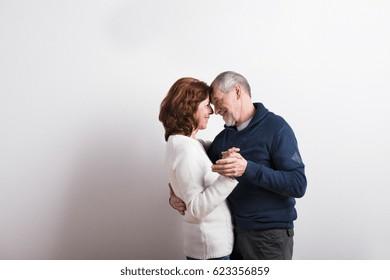Beautiful senior couple in love dancing. Studio shot.