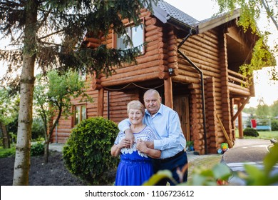 Beautiful senior couple in love hugging at spring garden, blooming tree with wooden country house on background outside. Love, life, relationship concept.