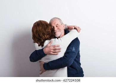 Beautiful senior couple in love hugging. Studio shot.