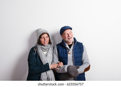 Beautiful senior couple in love in winter clothes. Studio shot.