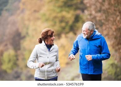 Beautiful senior couple running outside in sunny autumn nature