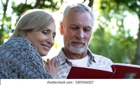 Beautiful senior family couple viewing photoalbum, pleasant youth memories