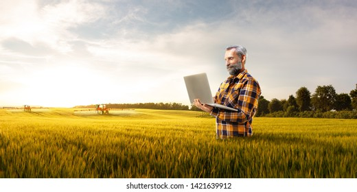 Beautiful senior farmer use new technology for agronomy. Hi holds laptop