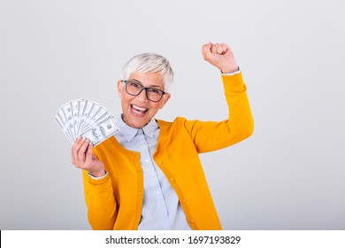 Beautiful senior lady holding a bunch of $100 bills with surprised facial expression. Mature woman winning money. Finances and people concept, senior woman holding hundreds of dollar money banknotes
