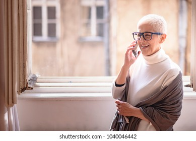 Beautiful senior lady talking on her cell phone, standing next to a big home window, enjoying her chat