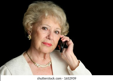 A beautiful senior lady talking on the phone with a serious expression.