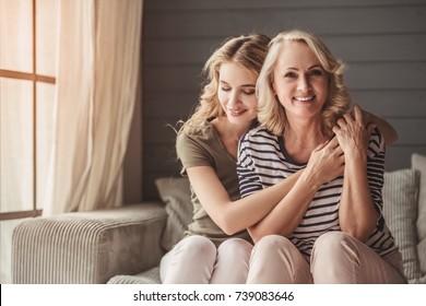 Bela sênior Mom e ela adulto filha são abraços e sorrindo enquanto sentado no sofá no Casa