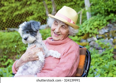 beautiful Senior smiling woman with straw hat  hugging her dog in the  mountain