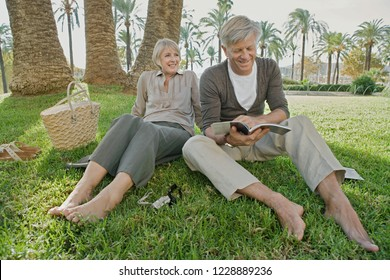 Beautiful senior tourist couple relaxing on green grass with bare feet, smiling sunny outdoors vacation. Mature people reading travel book, leisure recreation lifestyle, enjoying adventure trip.