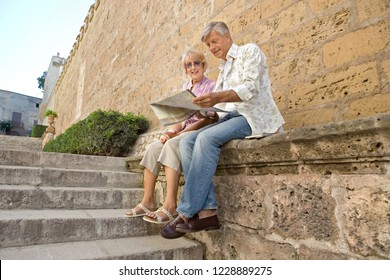 Beautiful senior tourist couple sitting at stone monument reading map, sightseeing on holiday, outdoors. Mature man and woman visiting sights, travel leisure recreation lifestyle.