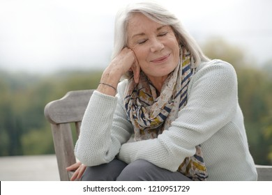 Beautiful senior womam sitting outdoors looking peaceful