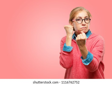Beautiful senior woman with an angry, aggressive and menacing pose, ready for the fight, showing fists furiously and belligerently.