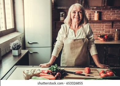 Beautiful senior woman in apron is looking at camera and smiling while cooking in kitchen