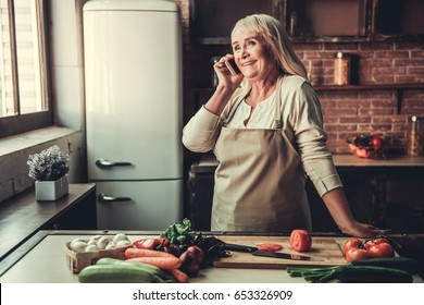 Beautiful senior woman in apron is talking on the mobile phone and smiling while cooking in kitchen