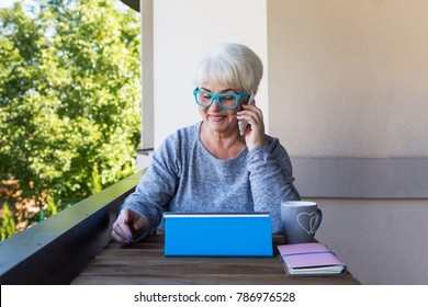 A beautiful senior woman with blond hair runs a business at home. View of the terrace. Sunny day.