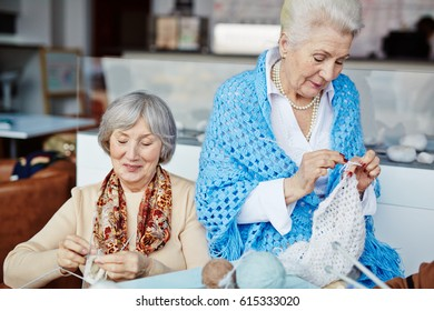 Beautiful senior woman in blue knitted shawl crocheting while her cheerful best friend sitting next to her and knitting with help of four needles