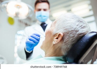 Beautiful senior woman at dentist having dental treatment at dentist's office.