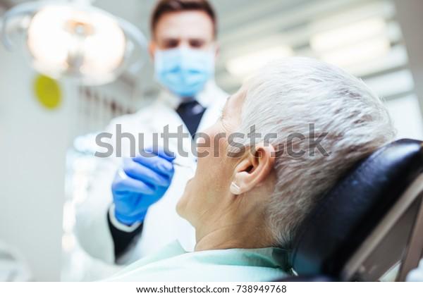Beautiful senior woman at dentist having dental treatment at dentist's office.