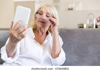Beautiful senior woman in eyeglasses reading message on smartphone and smiling while sitting on couch at home