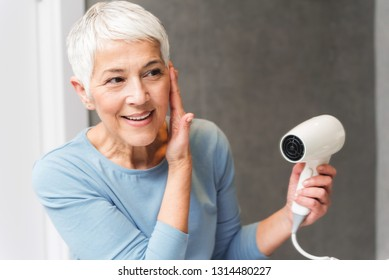 Beautiful senior woman with gorgeous smile and glowing skin drying her short gray hair at home