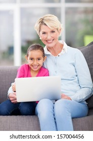 beautiful senior woman and her granddaughter using laptop computer at home