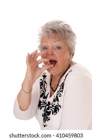 A beautiful senior woman in her seventies holding a vitamin pill, in closeupisolated for white background.