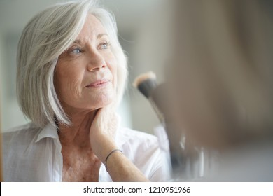 Beautiful senior woman infront of mirror with make up brushes
